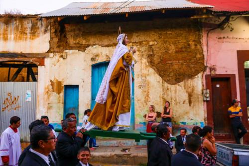 Transgeneracional intercultural, gratuito, preparado por el pueblo, para el pueblo y para sus visitantes. Los Santos representados marchan entre el cableado eléctrico atrayendo miradas, pensamientos, motivaciones y culpas.